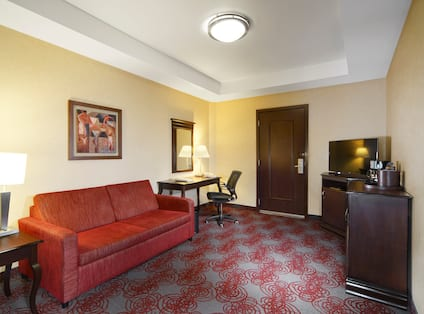 Guest Suite Lounge Area with Sofa, Work Desk and HDTV