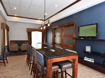 Lobby Seating Area with Tall Table, Chairs and TV