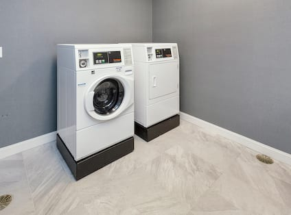 Guest Laundry Room with Two Coin-Operated Washing Machines