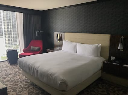One King Bed with Red Chair and Ottoman and Floor to Ceiling Window with View
