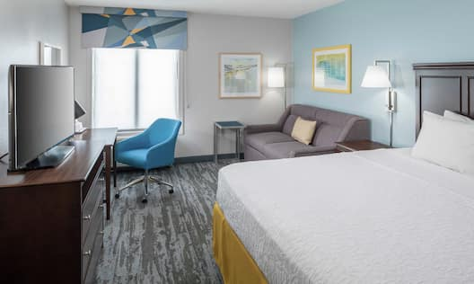 Guestroom with King Bed, Lounge Area, Work Desk, and Room Technology