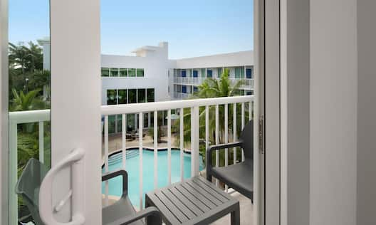 Balcony with two chairs and a table offering view of the pool area