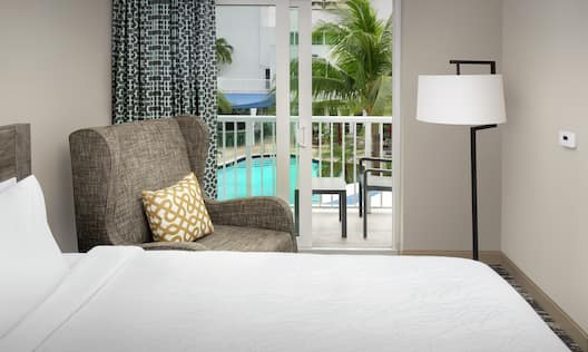 Guestroom with Bed, Lounge Area, and Outside View of Pool