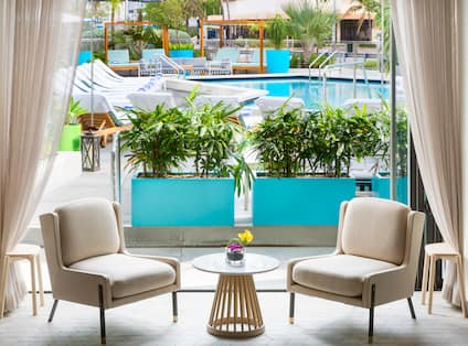 Lobby Seating Area with Two Soft Chairs, Small Table and Outdoor Pool