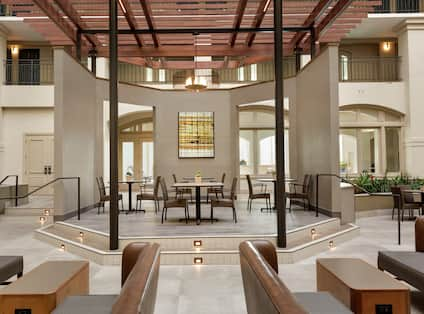 Bright hotel atrium featuring stylish design and ample seating for guests to relax.