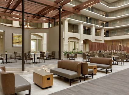 Open concept hotel atrium featuring stylish design and ample seating for guests to relax.