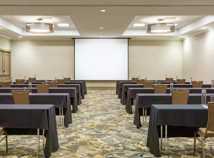 Spacious ballroom  featuring classroom setup with tables, chairs, and projector screen at front of room.