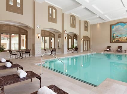 Beautiful indoor pool featuring ample seating, fresh rolled towers, and high coffered ceilings.