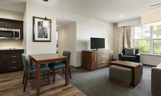 suite living area with kitchen area and chairs