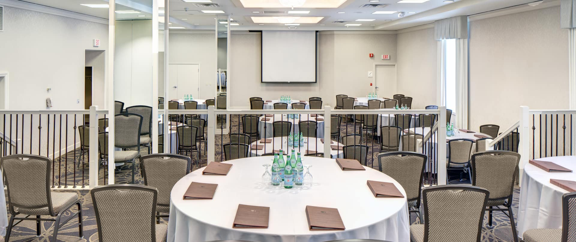 Cabaret Setup With Round Tables and Chairs Facing Presentation Screen in Split Level Meeting Space