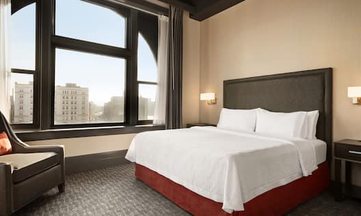 Suite Bedroom with King Bed, Chair and Outside View