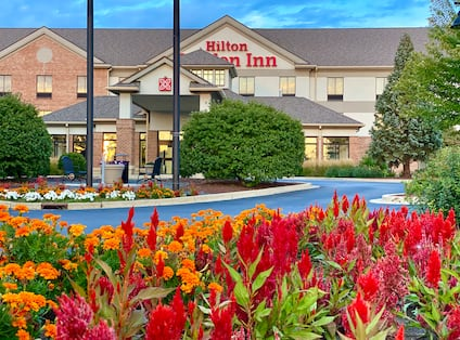 Hilton Garden Inn Hotel Exterior with Trees and Colorful Flowers