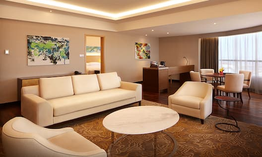 Two Armchairs, Coffee Table, Wall Art Above Sofa, Open Doorway to View of Bedroom, Work Desk, and Seating for Four at Dining Table by Large Window With Long Drapes in Presidential Suite Living Room