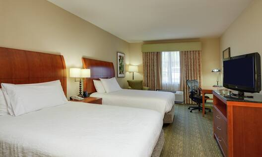 Double Queen Guestroom with Two Beds, Lounge Area, Work Desk, and Room Technology