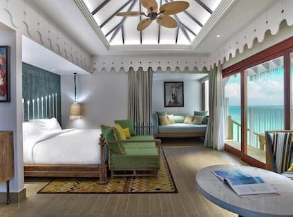 Overwater Villa Bedroom with Bed, Lounge Area, and Outside View