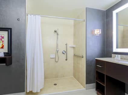 Accessible Bathroom with Roll In Shower Grab Bars and View of Vanity Area with Mirror