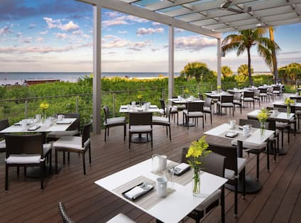 Square tables with yellow flowers and sunset in background at Deck Restaurant