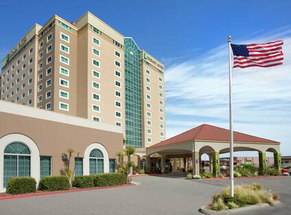 Embassy Suites hotel exterior featuring porte cochere, American flag on pole, and convention center.