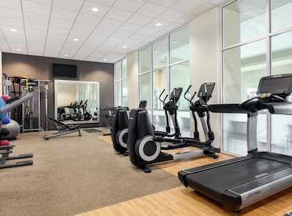 Bright on-site fitness center fully equipped with cardio machines, free weights, and resistance training equipment.