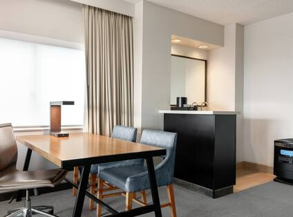 Bright living area incorner PURE suite featuring dining table, wet bar, and air purifier.