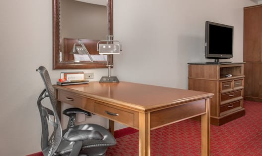 Work Desk and Ergonomic Chair with HDTV in the Background