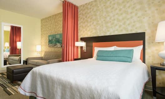 Queen Bed and Lounge Area in Studio Suite