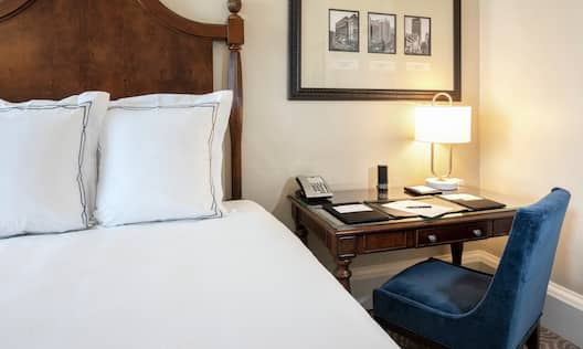 Bed in room with workdesk and chair