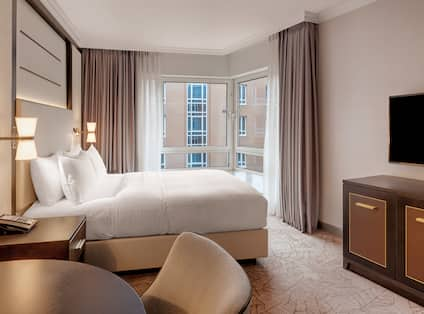 Hotel Guestroom with One Queen Bed, TV, Dining Table and Corner Window with Outside View