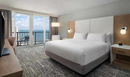 Bed in room with TV and balcony