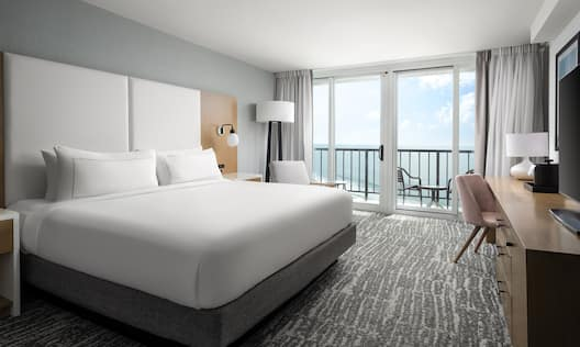Guest Room with Large Bed Desk and Balcony with Beach View