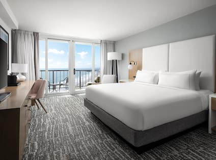 Large Bed in Guest Room with Beach View from Balcony