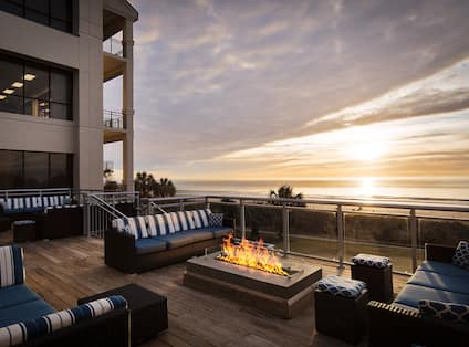 Outdoor Patio Seating Area with Sofas and Firepit at Daytime