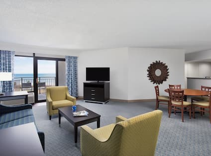 Guest Suite Lounge Area with Armchairs, Coffee Table, Sofa, Outdoor Balcony and HDTV