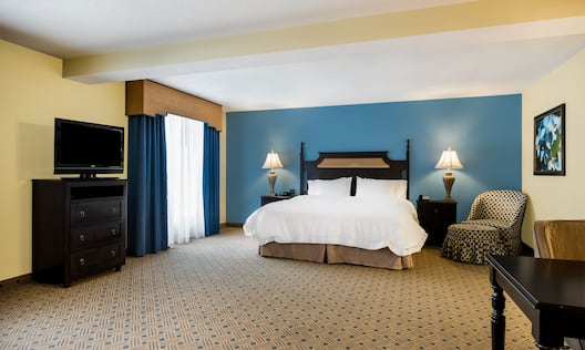 Studio with king bed, nightstands, lamps, work desk, and TV