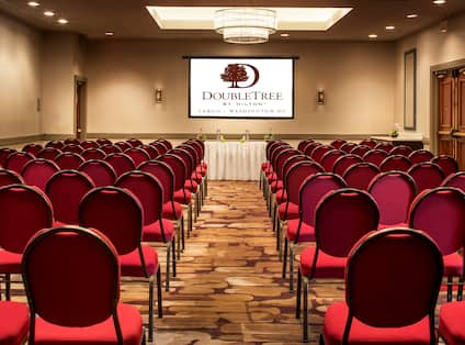 Meeting Room Arranged Theater Style With Rows of Red Chairs Facing Speaker's Table With White Linens and Presentation Screen
