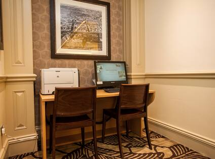 Wall Art Above Work Desk With Computer, Printer, and Two Chairs in Business Center