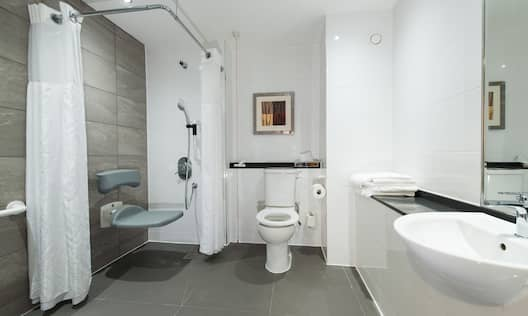 Roll-In Shower With Curtains, Shower Seat, Grab Bars Handheld Showerhead, Wall Art Above Toilet, and Illuminated Vanity Mirror, Sink, and Fresh Towels in Accessible Guest Bathroom