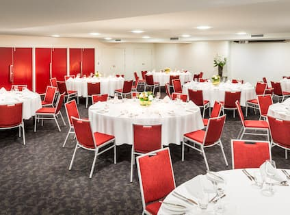 Banquet Room with Red and White Table Settings