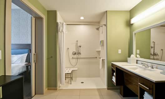Accessible Guest Bathroom Vanity with Roll-In Shower with Handrails and Bench