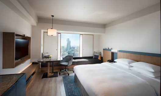 Bed, Desk and TV in Room with City View