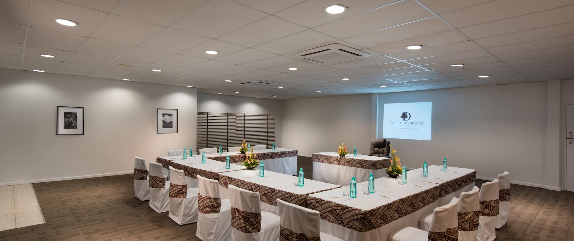 Meeting Space With Wall Art, U-Shaped Table and Chairs, Audio/Visual Equipment, and Speaker's Table