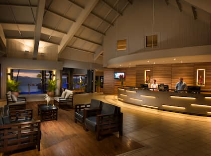 Illuminated Lobby With Lounge Seating, Sunset View of Ocean, and Two Staff Members Behind Front Desk