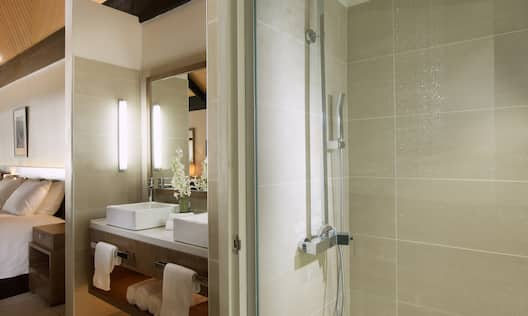 Shower With Glass Doors, Vanity Mirror, Double Sinks, Toiletries, Fresh Towels and View of Bed in Bure