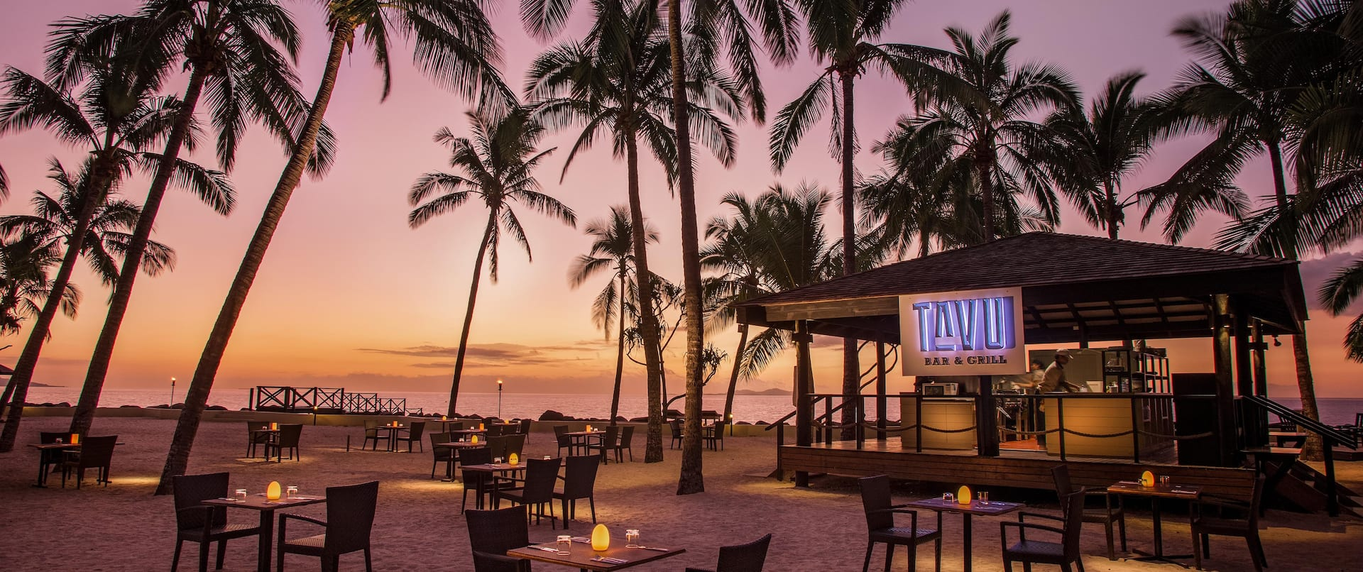 Sunset View of Candlelit Tables and Chairs Surrounded by Sand and Palm Trees at Tavu Grill