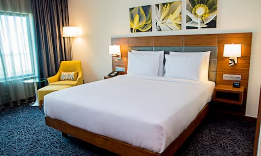 One King Bed Guest Bedroom with Armchair and Footrest