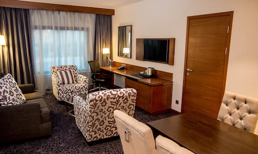 Guest Suite Lounge Area with Armchairs, Sofa, Work Desk and Wall Mounted HDTV