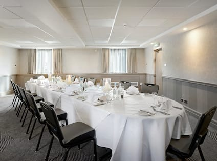 Windows With Sheer Drapes, 14 Place Settings on Long Table With White Linens Set Up for Private Dinner in Meeting Space