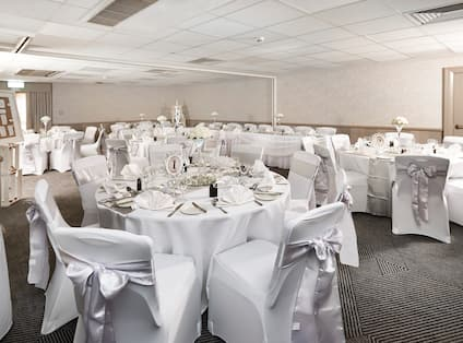 Place Settings, Wine Glasses, Photo Frame and Napkins on Round Tables With White Linens Decorated for Wedding Reception in Oxford Suite