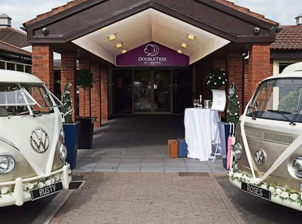 Two Gold and White Volkswagen Vans Decorated With White Ribbons and Flowers Parked by Wedding Entrance