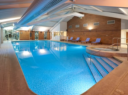 Illuminated Indoor Pool and Whirlpool With Lounge Chairs, Glass Door, and Large Windows With View into Fitness Center